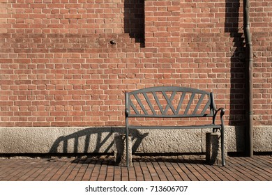 Old rusty steel bench with red brick wall  horizontall image