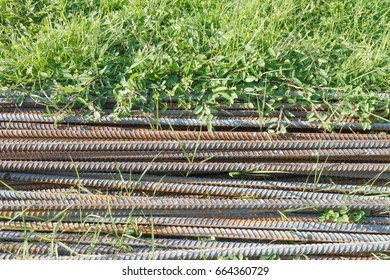 Old rusty steel construction rods on the grass.