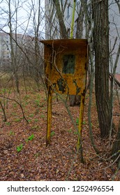 Old rusty telephone booth on overgrown tree street of abandoned ghost town of Pripyat, Chernobyl NPP exclusion zone, Ukraine