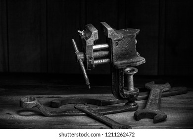 Old rusty tool in the dark room, totally dark place, playing with lights, old stuff, vice, carbine, keys on wooden table. black and white photo.