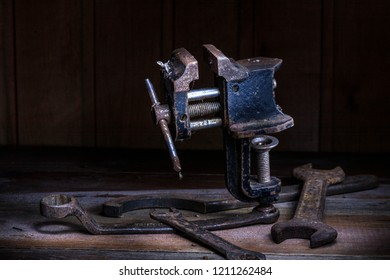 Old rusty tool in the dark room, totally dark place, playing with lights, old stuff, vice, carbine, keys on wooden table.