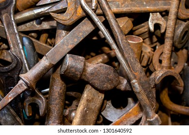 Old rusty tools are in disarray. In the foreground a hammer, a wrench and a chisel. Background texture closeup.