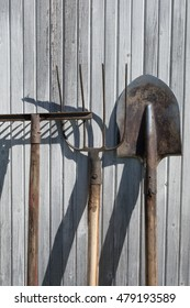 The old rusty tools, implements or household equipment on wooden background.