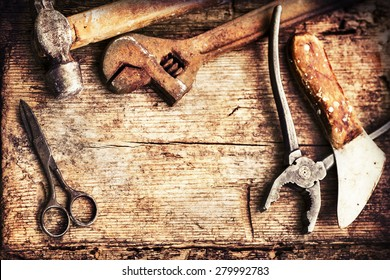 Old rusty tools, scissors, hammer on old wooden table background, fathers day background.
