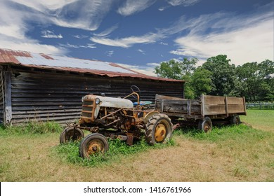 An old rusty tractor by a weathered barn in a field