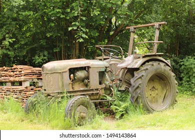 old and rusty tractor surrounded by grass and trees