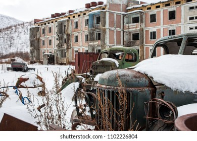 Old rusty truck bodies in abandoned town in winter