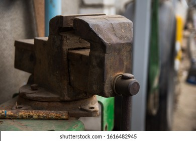 An old rusty vise, located in the inner yard of the old village house. Workshop concept. Tools and hardware for everyday. Construction and repair. Selective focus