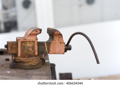 old rusty vise on a metal table