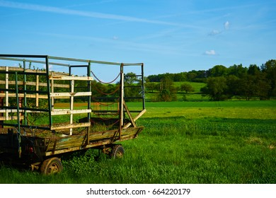 Old rusty wagon in a green field with a blue sky in the background
