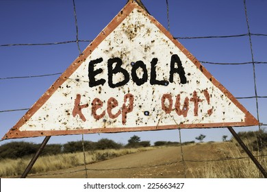 old rusty warning triangle at a fence in Africa  with the words Ebola keep out