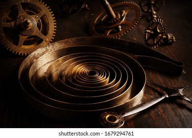 Old rusty watch parts with gear wheels in the dark. Repair of vintage brass clock.