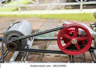 Old and rusty water pump motor with red pulley wheel and belt, Dirty water pump and belt