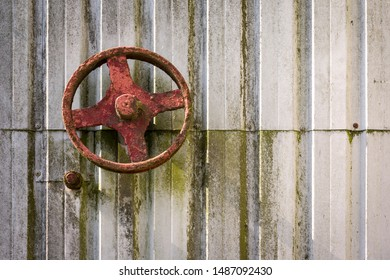 An old rusty wheel on a sheet metal wall serves as a shut-off valve for a lock gate.