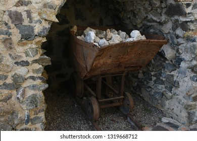 Old rusty wheelbarrow charged with mineral stones