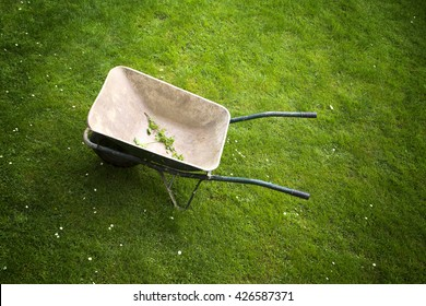 Old rusty wheelbarrow on a green grass field background. Top view perspective used.