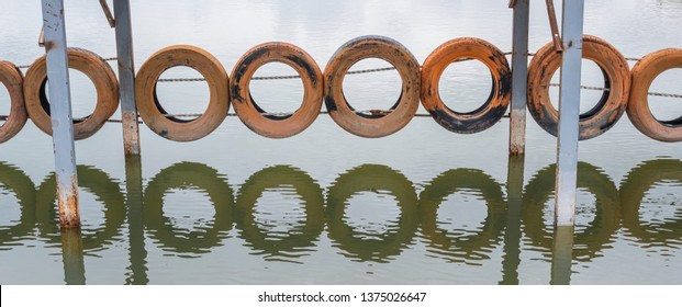 Old, rusty wheels hanging on the bridge ropes, above the water