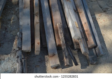 Old and rusty wood removed from the building and piled up on the ground, preapred for moving out of the area