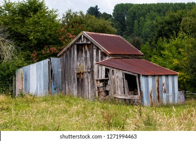 An old and rusty wooden and corrugated iron building stands abandoned in a farmers field in rural New Zealand