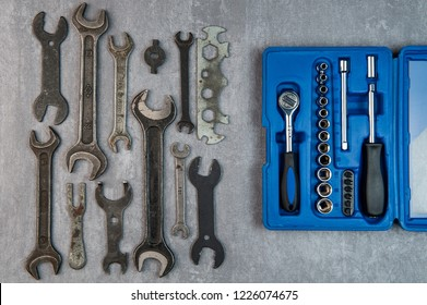 Old rusty wrenches vs new instruments in blue case on grey background. Concept old versus new.