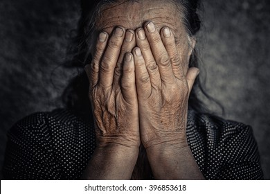 Old sad poor woman. Closeup portrait depressed stressed thoughtful senior lady elderly gloomy worried covering face isolated dark background. Human face expressions emotions feelings reaction attitude