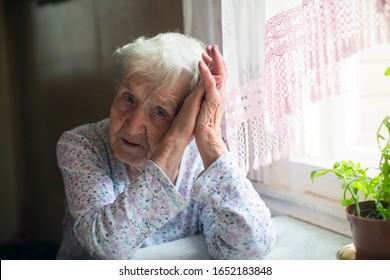 An old sad senior woman is sitting at a table in her house.