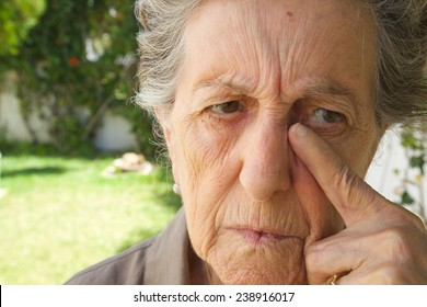 An old sad woman between 70 and 80 years old is drying the tears from her face. Garden background