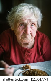 An old sad woman eats porridge. Portrait.