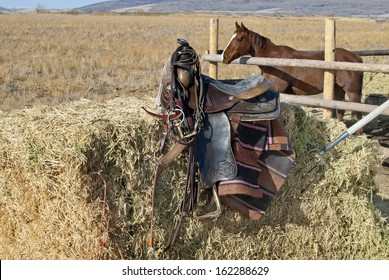 An old saddle and tack on a hay bale with a horse in a corral in the background on a western High Desert ranch in the Rocky Mountains.