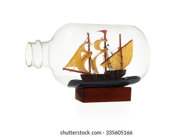 Old sailboat in glass bottle isolated on white background