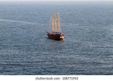 An old sailing ship rests in the calm waters just off shore
