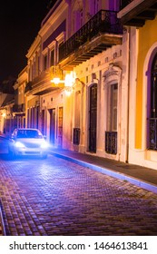 Old San Juan Puerto Rico street seen at night with old architecture and car in cobblestone street.
