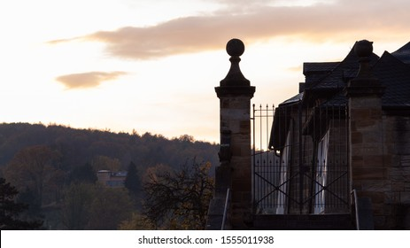 Old sandstone pillar and iron gate isolated, bright evening sky, with forest in background
