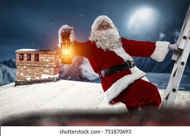 The old Santa Claus enters the roof of the house. Landscape of the mountains and the big moon. Visible big chimney on the roof.