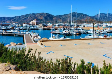 Old Sardinian Port and marina with ships at Mediterranean Sea in city of Villasimius in South Sardinia Island in Italy in summer. Cityscape with Yachts and boats