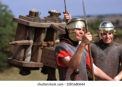 Old Sarum Fort Wiltshire UK 1995. Unidentified reenactors of the Roman period wear the armour of Roman Auxiliaries and stand guard next to a Scorpion siege weapon at a re-enactment event.