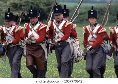 Old Sarum Salisbury UK 1996. A group of reenactors of the Napoleonic Wars wear period uniforms of British Fusiliers they charge muskets at the ready at a reenactment of the Battle of Waterloo 1815.
