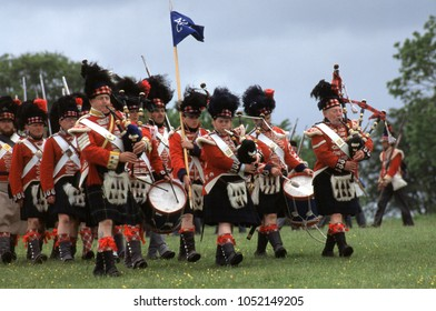 Old Sarum Wiltshire UK 1996. Unidentified reenactors wear the period uniform of Scots Highlanders of the Napoleonic War they march led by bagpipers at a re-enactment of the Battle of Waterloo 1815.
