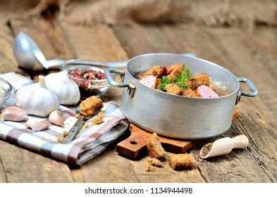 Old saucepan with garlic soup, fresh garlic bulbs, cloves, colored pepper, wooden spoon, croutons, lable and a towel on a rustic wooden table