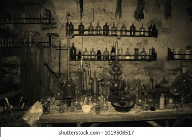 Old scary laboratory mining tools & measuring devices. Bottles in old pharmacy laboratory. Old vintage mini laboratory. Medieval drugs potion on dirty shelf, apothecary cabinet in pharmacy lab or shop