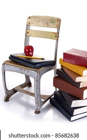 An old school chair holding a laptop with an apple and pencil on top beside a stack of hardbound books on a white background with reflection.