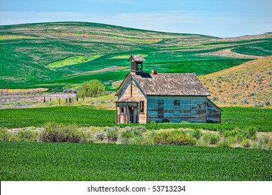 Old School House in green field with blue sky in abstract.