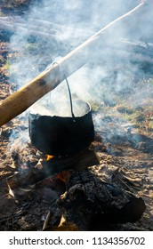 old school way of making tea outdoor. steam and smoke all around. black cauldron hang on the log above the fire place. wonderful taste of summer and hike in the woods experience