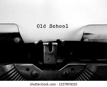 OLD SCHOOL word meaning old fashioned traditionalist die-hard methods; typewritten in black text on white paper on vintage obsolete technology manual typewriter machine.