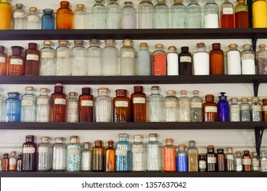 Old science laboratory shelves with chemical bottles and colorful reagents.
