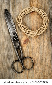 old scissors and hank of packthread on wooden background