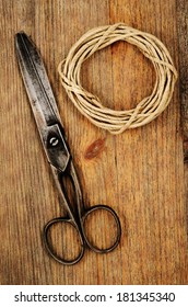 old scissors and hank of packthread on wooden background with Grunge Filter