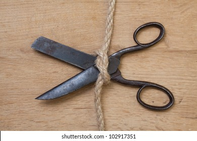 Old scissors on wood in rope knot