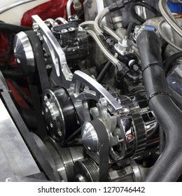 Old scool V8 turbo compressor motor engine in red tuned American muscle car - supercharger, belt on pulleys