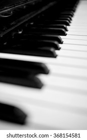 Old scratched dusty piano. Black and white image with selective focus